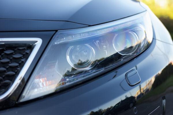 Luxury car headlight- closeup view, background.